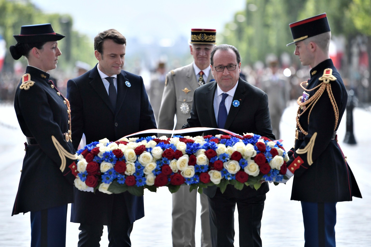 French President-elect Emmanuel Macron, second left, and outgoing President Francois Hollande lay a wreath of flowers at the tomb of the Unknown Soldier during a ceremony to mark the end of World War II at the Arc de Triomphe in Paris, Monday, May 8, 2017. Macron defeated far-right leader Marine Le Pen handily in Sunday's presidential vote, and now must pull together a majority for his year-old political movement by mid-June legislative elections. (Stephane de Sakutin, Pool via AP)