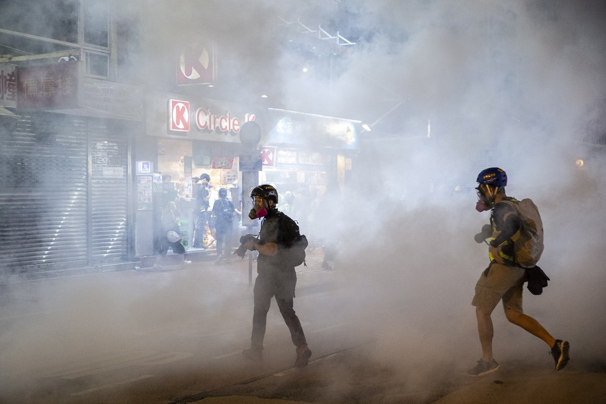 epa07859779 Members of the media photograph tear gas fired by riot police to disperse protesters in Yuen Long district, Hong Kong, China, 21 September 2019. Hong Kong has entered its fourth month of mass protests, originally triggered by a now suspended extradition bill to mainland China that have turned into a wider pro-democracy movement.  EPA/CHAN LONG HEI