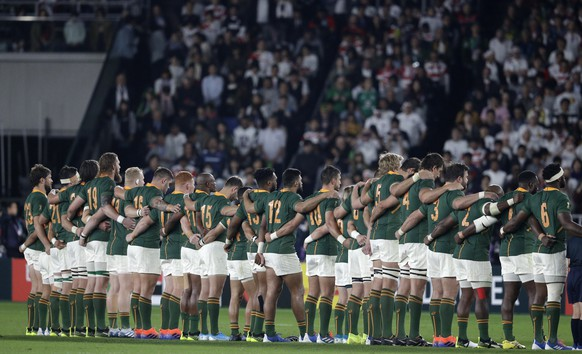 The South Africa team link arms before the start of the Rugby World Cup final at International Yokohama Stadium between England and South Africa in Yokohama, Japan, Saturday, Nov. 2, 2019. (AP Photo/Aaron Favila)