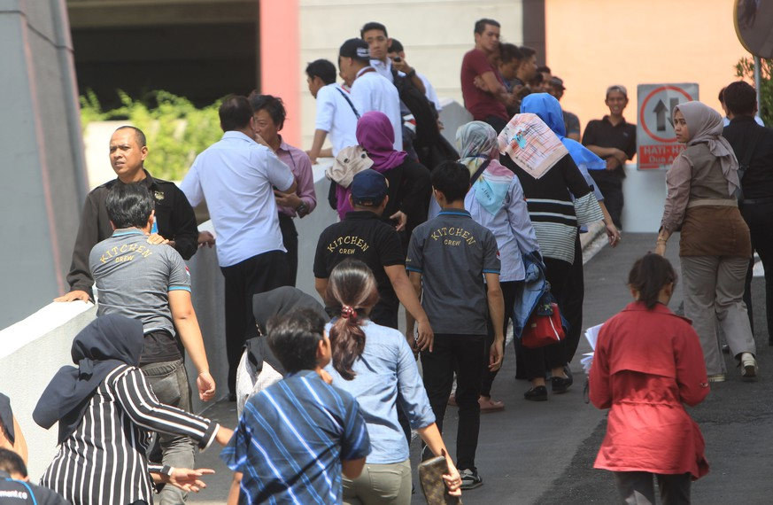 epa06466702 Employees walk outside a building after an earthquake caused office workers to flee swaying buildings, in Jakarta, Indonesia, 23 January 2018. Shakes were felt in Jakarta after a 6.0 magnitude earthquake hit 40 km south of Binuangeun, Indonesia, according to the United States Geological Survey (USGS).  EPA/ADI WEDA