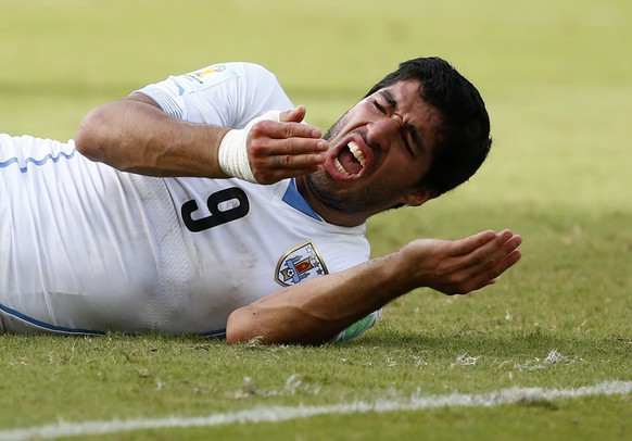 Uruguay's Luis Suarez reacts after clashing with Italy's Giorgio Chiellini during their 2014 World Cup Group D soccer match at the Dunas arena in Natal June 24, 2014. REUTERS/Tony Gentile (BRAZIL - Tags: SPORT SOCCER WORLD CUP TPX IMAGES OF THE DAY TOPCUP)