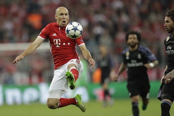 Bayern's Arjen Robben jumps for the ball against Real Madrid's Sergio Ramos during the Champions League quarterfinal first leg soccer match between FC Bayern Munich and Real Madrid, in Munich, Germany, Wednesday, April 12, 2017. (AP Photo/Matthias Schrader)