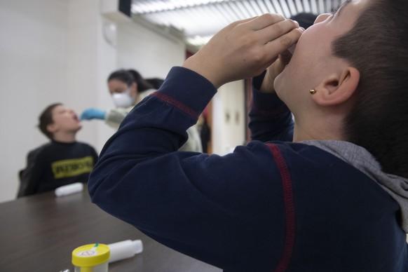 Schueler der staedtischen Grundschulen in Chiasso machen einen freiwilligen Covid-19 Speicheltest am Montag, 29. Maerz 2021 in Chiasso. Die Kinder nehmen dazu fuer einige Sekunden eine Fluessigkeit in den Mund, die sie anschliessend in einen  Speichelbehaelter spucken. (KEYSTONE/Ti-Press /Davide Agosta)