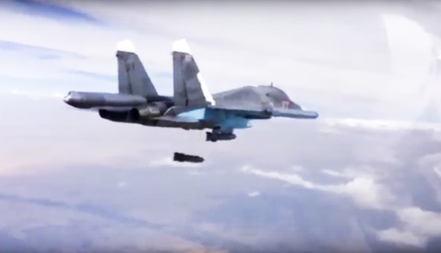 In this photo made from video footage provided by the Russian Defense Ministry on Wednesday, Dec. 9, 2015, a Russian Su-34 bomber drops bombs on a target. Russia has unleashed another barrage of airstrikes against targets in Syria, including the first combat launch of a new cruise missile from a Russian submarine in the Mediterranean Sea, the country's defense minister said Tuesday. (Russian Defense Ministry Press Service via AP)