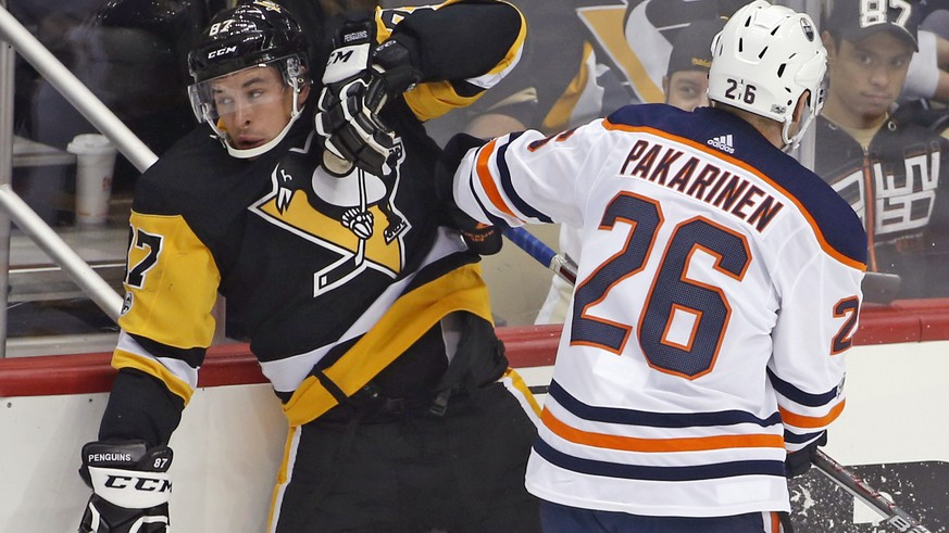 Edmonton Oilers' Iiro Pakarinen (26) checks Pittsburgh Penguins' Sidney Crosby (87) in the first period of an NHL hockey game in Pittsburgh, Tuesday, Oct. 24, 2017. (AP Photo/Gene J. Puskar)