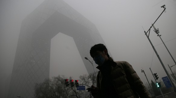 epa05073521 (FILE) A file picture dated 01 December 2015 shows a man wearing a mask in front of the China Central Television (CCTV) Tower during a hazy day in Beijing city, China. Beijing issued a red alert for smog on 18 December 2015, urging schools to close and residents to stay indoors for the second time in 10 days. Restrictions begin on 19 December and last until 22 December, the city's emergency management headquarters announced on the Beijing government website. Measures included pausing factory work and restricting road traffic, except electric vehicles. The alert reflects a forecast of three days of PM2.5 - airborne particulate matter 2.5 microns and smaller - levels above 200 micrograms per cubic meter. PM2.5 pollution is fine enough to penetrate deep into the lungs, and is associated with increased risk of heart attack, stroke, lung cancer and asthma.  EPA/WU HONG
