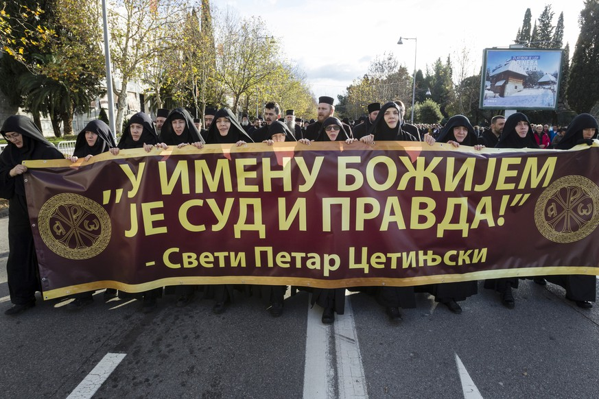 Serbian Orthodox Church clergy in Montenegro march and hold a banner reading: ''Judgment and Justice are in God's name'' as they protest the planned adoption of a religious law that they say will pave the way to strip the church of its property, in Podgorica, Montenegro, Tuesday, Dec. 24, 2019. Montenegro's pro-Western president has accused the church of promoting pro-Serb policies in Montenegro and seeking to undermine the country's statehood since it split from Serbia in 2006. (AP Photo/Risto Bozovic)