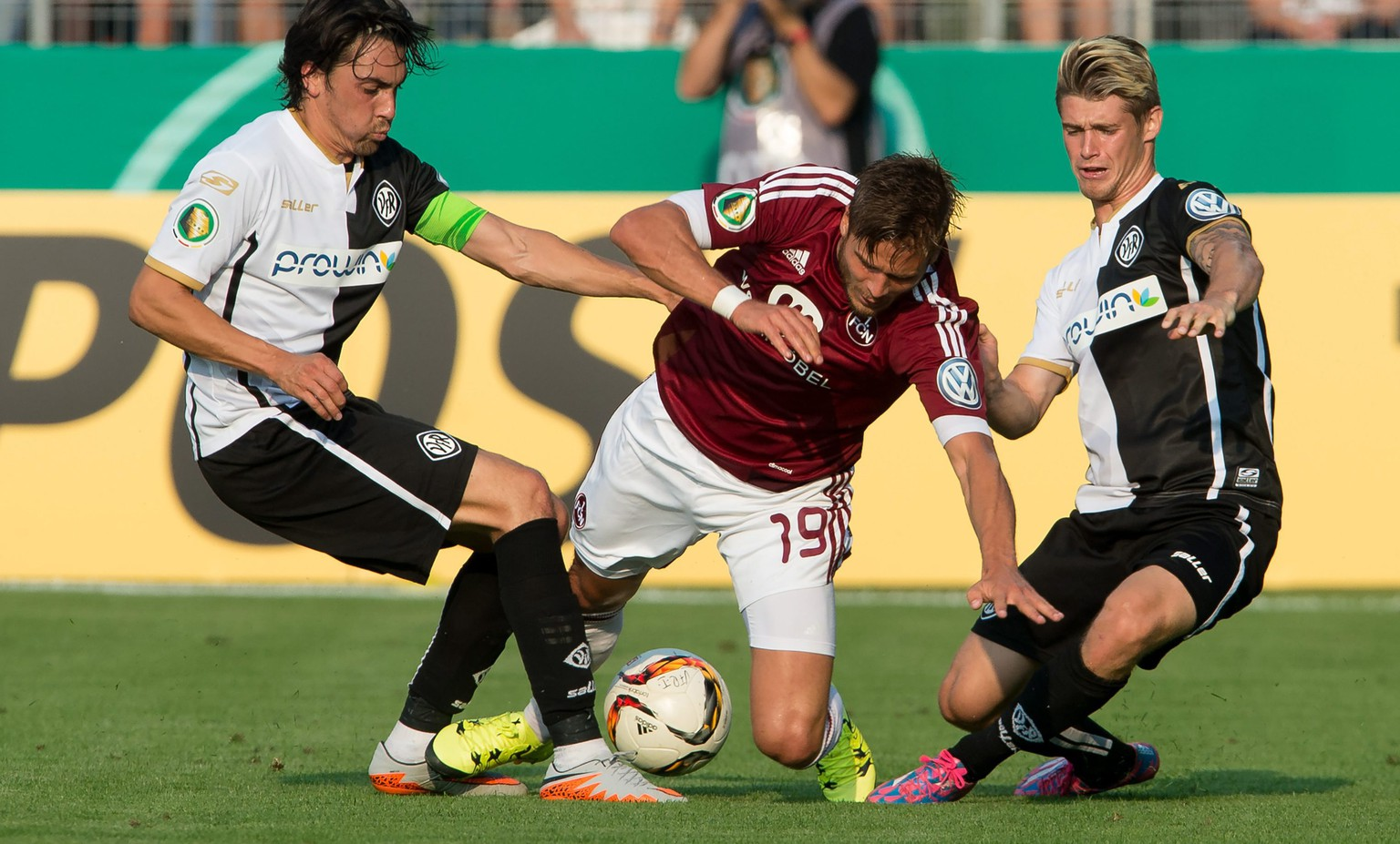 epa04879396 Aalen's Markus Schwabl (L) and Dennis Chessa in action against Nuernberg's Rurik Gislason (C) during the German soccer DFB Cup first round match between VfR Aalen and 1. FC Nuernberg at the Scholz Arena in Aalen, Germany, 10 August 2015. 