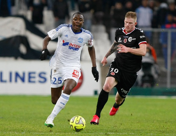 Marseille's French midfielder Giannelli Imbula, left, challenges for the ball with Reims' forward Gaetan Charbonnier,  during the League One soccer match between Marseille and Reims, at the Velodrome Stadium, in Marseille, southern France, Friday,  Feb. 13, 2015. (AP Photo/Claude Paris)