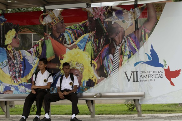 A couple of high school students wait for a bus at a stop decorated with a advertisement announcing the upcoming VII Summit of the Americas in Panama City, Wednesday, April 8, 2015. Panama City will host the Summit of the Americas on April 10-11. (AP Photo/Arnulfo Franco)
