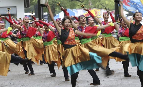 "Participants perform ""yosakoi"" folk dance as they parade through Tokyo streets during an annual ""Yosakoi"" festival Saturday, Aug. 29, 2015. Yosakoi is a unique style of a Japanese traditional summer dance movements with modern music. (AP Photo/Koji Sasahara)"