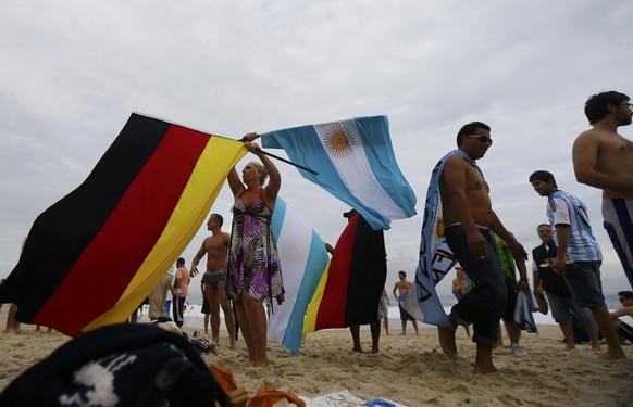 A woman waves German and Argentine flags on Copacabana beach ahead of Sunday's World Cup final match between Argentina and Germany in Rio de Janeiro July 11, 2014.  REUTERS/Ricardo Moraes (BRAZIL  - Tags: SPORT SOCCER WORLD CUP)