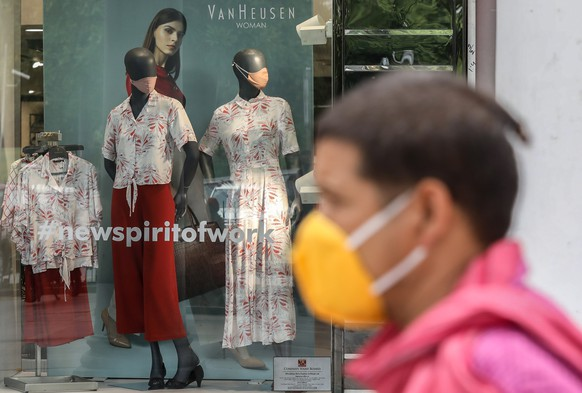 epa08517848 Mannequins with protective masks are kept inside a garments showroom as an Indian man wearing a protective face mask walks in New Delhi, India, 30 June 2020. Countries around the world are taking measures to stem the spread of the SARS-CoV-2 coronavirus, which causes the COVID-19 disease.  EPA/RAJAT GUPTA