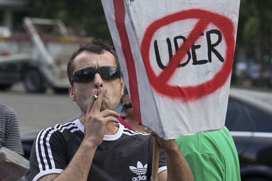 In this photo taken on June 11, 2014, a taxi driver protests against Uber during a 24 hour taxi strike in Madrid, Spain. In a statement Saturday July 22, 2017, the city of Madrid has asked Spain's anti-trust watchdog to investigate whether Uber's new airport transport service violates fair competition laws saying tariffs may violate several articles of the Law of Unfair Competition and consumer rights if they are below the cost of providing the service. (AP Photo/Paul White)