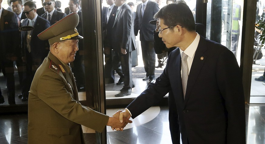 Hwang Pyong So, left, vice chairman of North Korea's National Defense Commission, shakes hands with South Korean Unification Minister Ryoo Kihl-jae upon his arrival at a hotel in Incheon, South Korea, Saturday, Oct. 4, 2014. Hwang, North Korea's presumptive No. 2 and other members of Pyongyang's inner circle made a surprise trip Saturday to South Korea for the close of the Asian Games, Seoul officials said, a visit that will include the rivals' highest level face-to-face talks in five years. (AP Photo/Yonhap, Shin Jun-hee) KOREA OUT