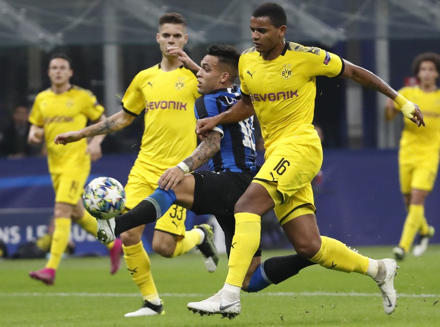 Inter Milan's Lautaro Martinez, centre, controls the ball between Dortmund's Julian Weigl, left, and Dortmund's Manuel Akanji, right, during the Champions League, Group F soccer match between Inter Milan and Borussia Dortmund at the San Siro stadium in Milan, Italy, Wednesday, Oct.23, 2019. (AP Photo/Antonio Calanni)