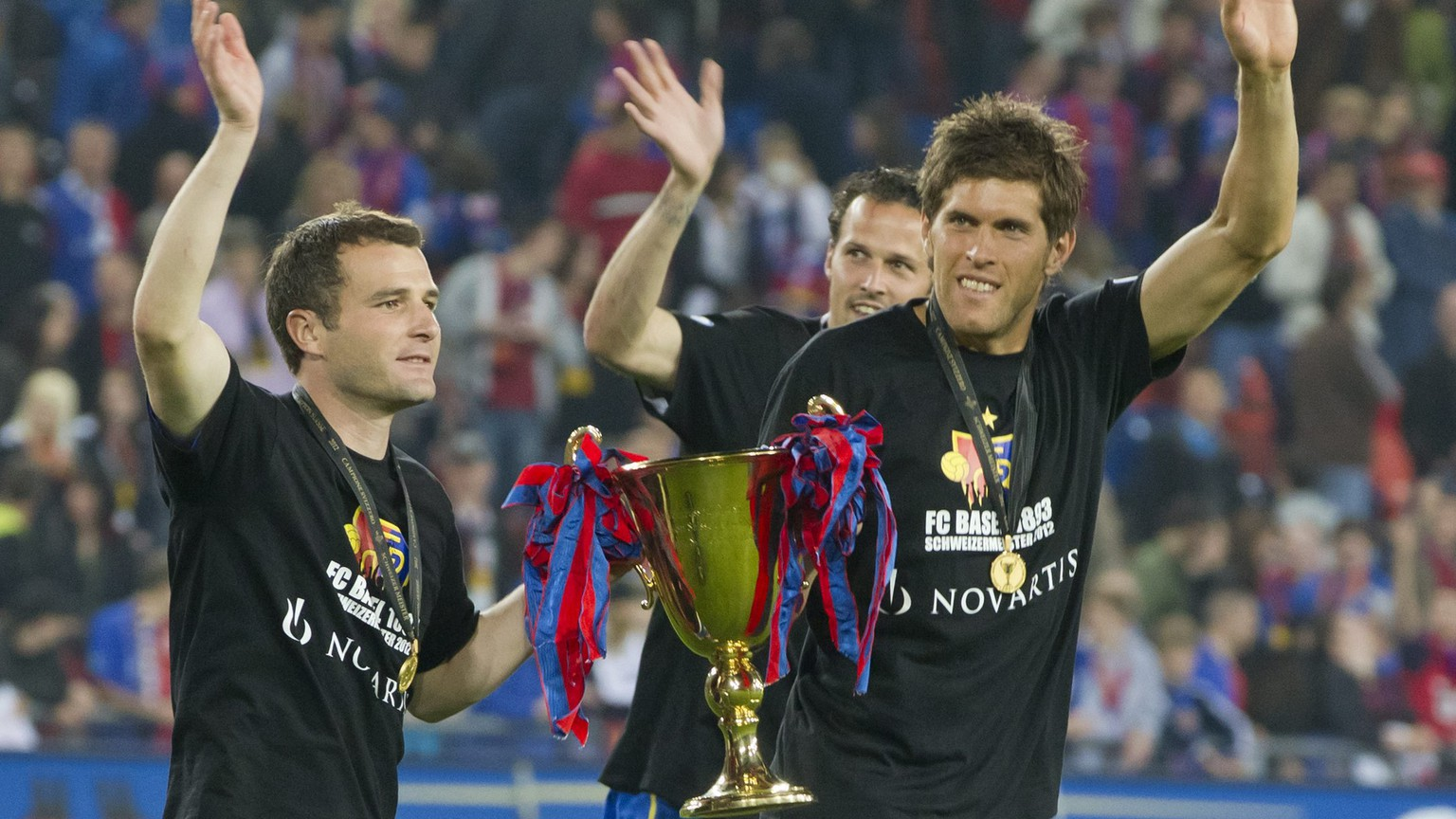 Basel's Alexander Frei, Marco Streller and Benjamin Huggel, from left, celebrate with their Trophy after the Super League soccer match between FC Basel and BSC Young Boys at the St. Jakob-Park stadium in Basel, Switzerland, on Wednesday, May 23, 2012. (KEYSTONE/Alessandro Della Bella)