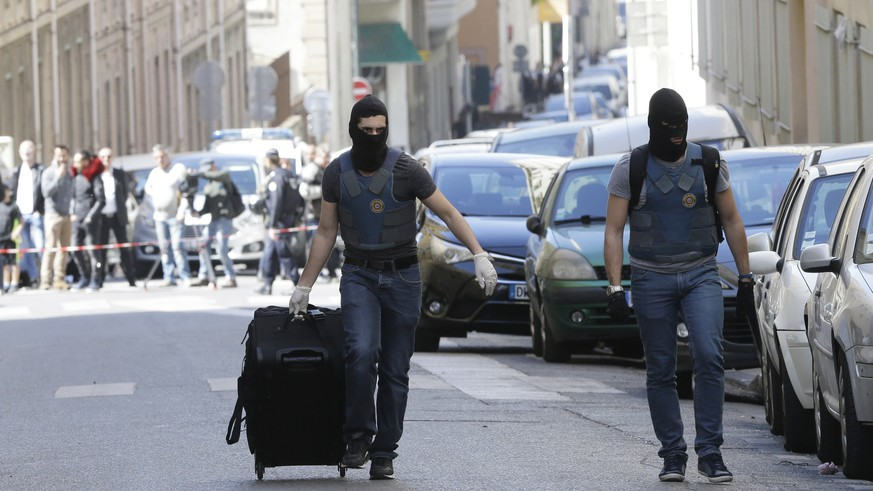 A hooded elite police officers pulls a suitcase after searches in Marseille, southern France, Tuesday, April 18, 2017. The French interior minister says police have arrested two suspected radicals who were allegedly preparing an