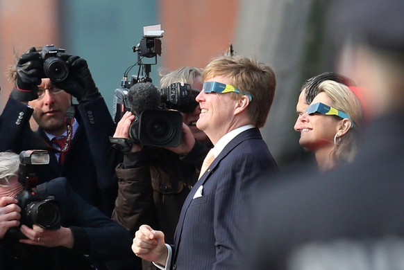 epa04670840 Queen Maxima and King Willem-Alexander of the Netherlands look at the solar eclipse through special glasses at the Fish Market inHamburg, Germany, 20 March 2015. The royal couple is on a two-day working visit of Northern Germany. A Partial Solar Eclipse is seen in Europe, northern and eastern Asia and northern and western Africa on 20 March with the eclipse starting at 07:41 UTC and ending at 11:50 UTC.  EPA/MALTECHRISTIANS