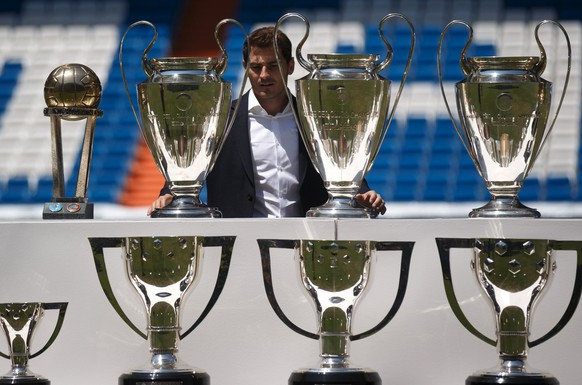 Departing Real Madrid captain and goalkeeper Iker Casillas poses surrounded by trophies at an official send-off at the Bernabeu stadium in Madrid, Spain, July 13, 2015. Several hundred Real Madrid fans chanted for president Florentino Perez to resign at an official send-off for goalkeeper and captain Iker Casillas at the Bernabeu stadium on Monday.  Real held the presentation following criticism over the surreal nature of Casillas's tearful news conference on Sunday, when he appeared to be alone in the stadium press room to read out a farewell statement.  REUTERS/Andrea Comas
