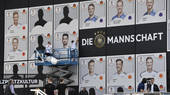 Workers stick posters with the portraits of German national players on the front of German Football Museum in Dortmund, Tuesday, May, 15, 2018 after the presentation of Germany's team for the Soccer World Cup in Russia. (AP Photo/Martin Meissner)