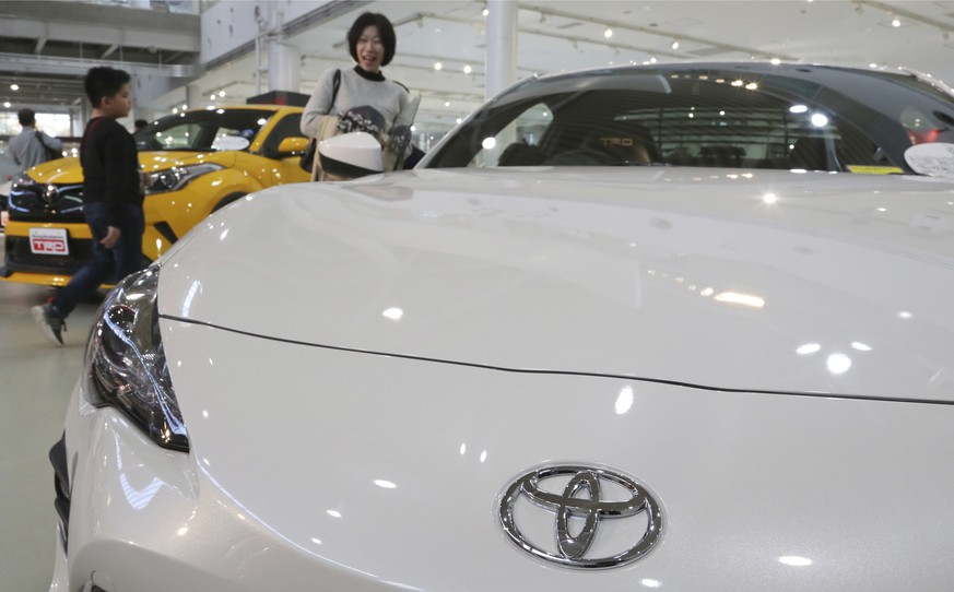 In this Nov. 13, 2017 photo, visitors take a look at a Toyota car at its showroom in Tokyo. Toyota plans to offer more than 10 purely electric vehicle models in its lineup by the early 2020s, marking the Japanese automaker's commitment to that growing technology sector.  Toyota Motor Corp. now offers no purely electric vehicles, although it leads in hybrid models, which switch between an electric motor and a gas engine. (AP Photo/Koji Sasahara)