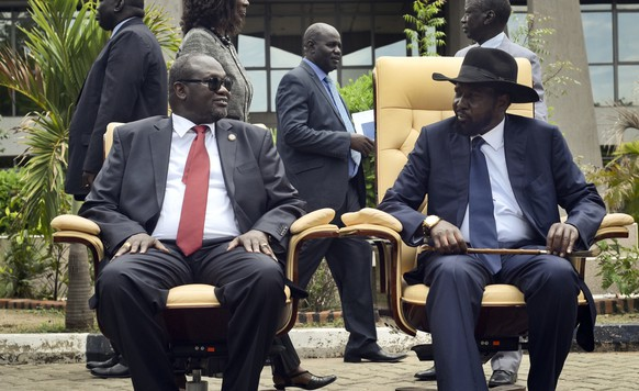 FILE - In this Friday, April 29, 2016 file photo, then South Sudan's First Vice President Riek Machar, left, looks across at President Salva Kiir, right, as they sit to be photographed following the first meeting of a new transitional coalition government, in the capital Juba, South Sudan. Kiir on Thursday, Aug. 9, 2018 was reported by the South Sudan Broadcasting Corporation to have granted amnesty to armed opposition leader Riek Machar and all rebel groups, days after signing a power-sharing agreement in the latest effort to end a five-year civil war. (AP Photo/Jason Patinkin, File)