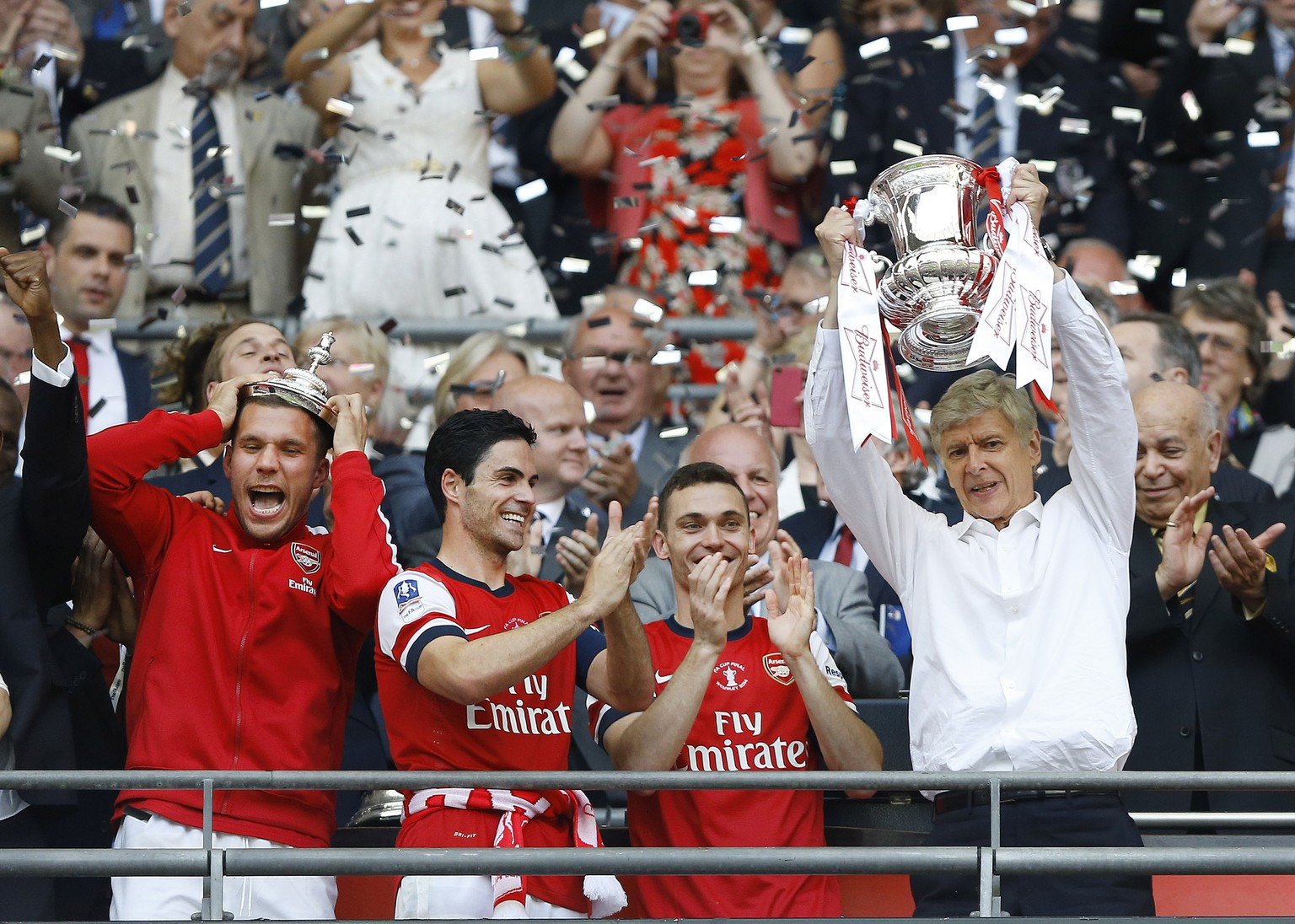 Arsenal's coach Arsene Wenger, right, hold the trophy aloft as he celebrates after his team won the English FA Cup final soccer match between Arsenal and Hull City at Wembley Stadium in London, Saturday, May 17, 2014. Arsenal won 3-2 after extra-time. (AP Photo/Kirsty Wigglesworth)