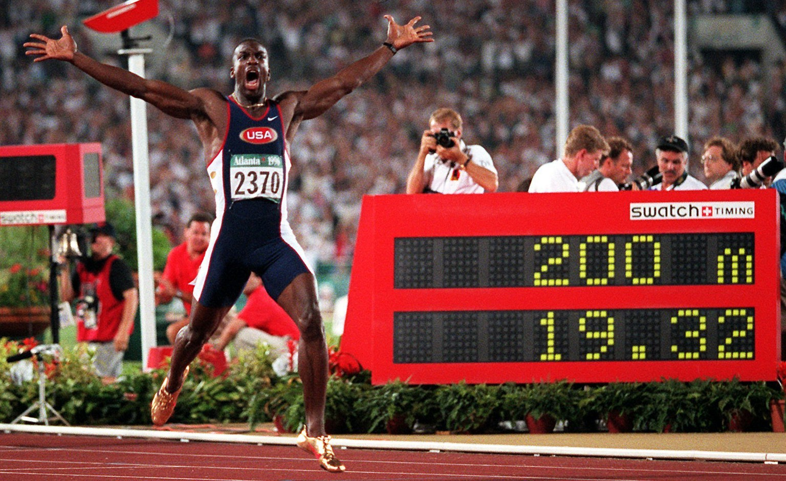 ADVANCE FOR SATURDAY, OCT. 1 - In this Aug. 1, 1996, file photo, Michael Johnson, of the United States, celebrates after he won the men's 200 meter final in a world record time of 19.32 at the 1996 Summer Olympic Games in Atlanta. Turner Field began its brief life as the main stadium for the 1996 Summer Olympics. After just two decades as the home of the Atlanta Braves, it's headed for another transformation. The Braves are moving to the suburbs next season, leaving the Ted to Georgia State University. (AP Photo/Doug Mills, File)