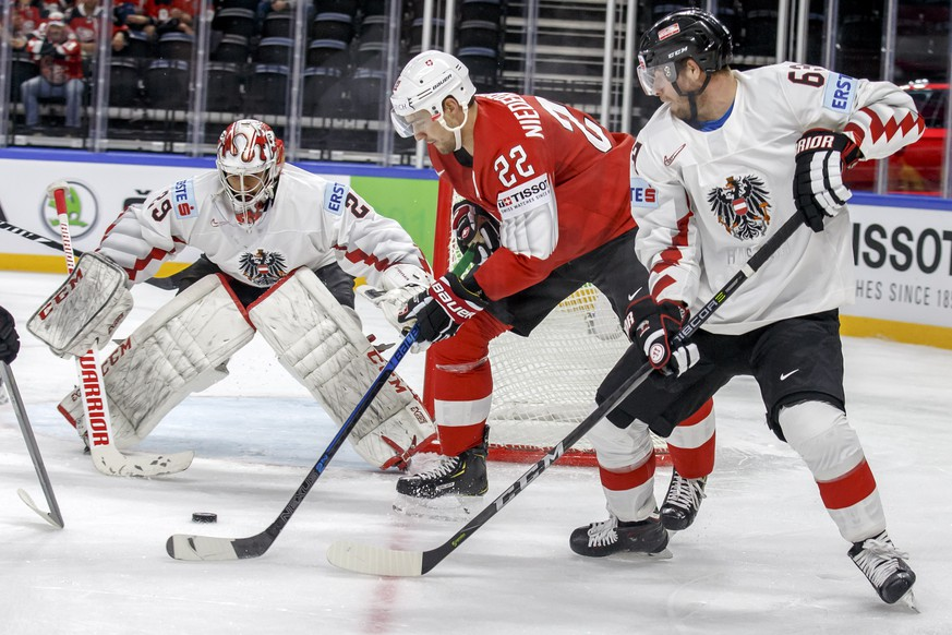 Switzerland's forward Nino Niederreiter, center, vies for the puck with Austria's defender Markus Schlacher, right, past Austria's goaltender Bernhard Starkbaum, left, during the IIHF 2018 World Championship preliminary round game between Switzerland and Austria, at the Royal Arena, in Copenhagen, Denmark, Saturday, May 5, 2018. (KEYSTONE/Salvatore Di Nolfi)