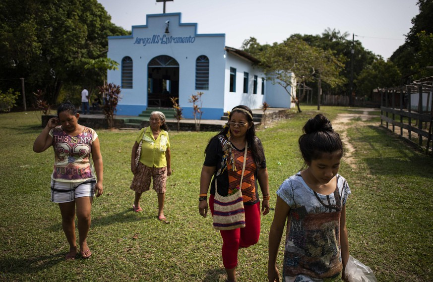 epa07128303 Indigenous educator of the 'Bare' ethinicity Ana Claudia Martins Tomas (2R), 40, whose indigenous name is 'Suri', heads to a polling station at the rural community of 'Nossa Senhora do Livramento', in Rio Negro, near Manaus, Brazil, 28 October 2018.  EPA/Raphael Alves