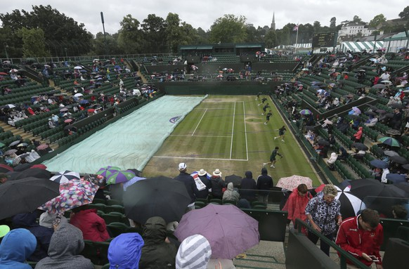The covers are put on court 2 as rain falls on day eight at the Wimbledon Tennis Championships in London Tuesday, July 11, 2017. (AP Photo/Tim Ireland)