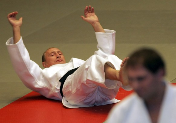 Russian President Vladimir Putin limbers up during a master class at a judo school in St. Petersburg, Saturday, Dec. 24, 2005. Putin, a judo black belt and a KGB veteran of 16 years, showed off his skills in the sport Saturday in nationwide television footage, giving a master class to students of a judo school in his home city. (KEYSTONE/AP Photo/Dmitry Lovetsky)