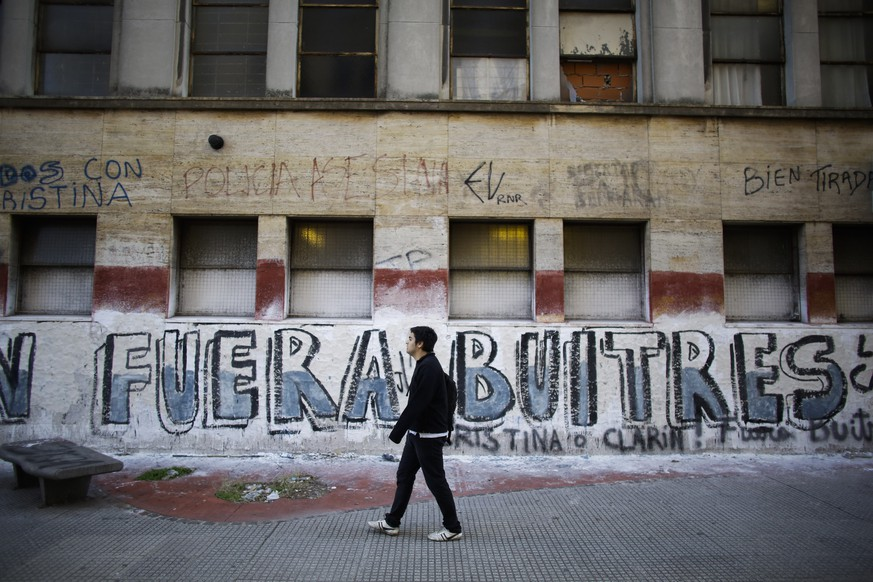 "A man walks by a graffiti that reads in Spanish, ""Out Vultures"" in reference to the dispute between the Argentine government and a U.S. hedge fund, known locally as ""vulture funds,""  in Buenos Aires, Argentina,  Monday, August 4, 2014. The collapse of talks with U.S. creditors sent Argentina into its second debt default in 13 years and raised questions about what comes next for financial markets and the South American nation's staggering economy. (AP Photo/Victor R. Caivano)"