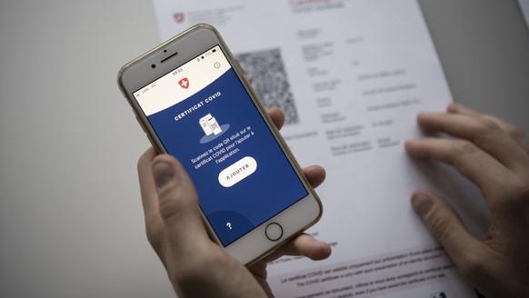 ZUM SCANNEN DES COVID-ZERTIFIKATS MITTELS DER COVID CERTIFICATE APP, STELLEN WIR IHNEN FOLGENDE BILDER ZUR VERFUEGUNG. WEITERE BILDER FINDEN SIE AUF visual.keystone-sda.ch --- Le certificat Covid Suisse est scanne avec un mobile, le mardi 15 juin 2021 a Zurich. Le certificat Covid contient le nom et prenom, la date de naissance, un numero de certificat, les details de la vaccination Covid 19 ou le resultat du test PCR ou du test rapide antigenique. Le code QR rend le certificat infalsifiable et garantit l'authenticite du certificat. (KEYSTONE/Christian Beutler)..Das Covid-Zertifikat Schweiz wird mit einem Mobiltelefon eingescannt, am Dienstag, 15. Juni 2021 in Zuerich. Das Covid-Zertifikat enthaelt neben Name, Vorname, Geburtsdatum und einer Zertifikatsnummer auch die Angaben zur Covid-19-Impfung, zur Genesung oder zum negativen PCR-Test- bzw. Antigen-Schnelltest-Resultat. Der im Covid-Zertifikat angezeigte QR-Code soll das Zertifikat dank einer elektronischen Signatur der Schweizerischen Eidgenossenschaft faelschungssicher machen und die Echtheit des Covid-Zertifikats garantieren. (KEYSTONE/Christian Beutler)