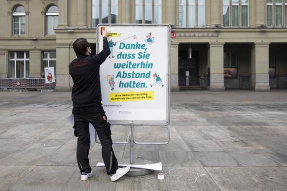 """Ein neues weisses BAG-Plakat mit der Verhaltensregel """"Danke, dass Sie weitherin Abstand halten"""", """"Merci de continuer a garder vos distances"""" im Umgang mit dem Coronavirus wird auf dem Bundesplatz installiert, am Montag, 1. Maerz 2021 in Bern. (KEYSTONE/Peter Klaunzer)"""
