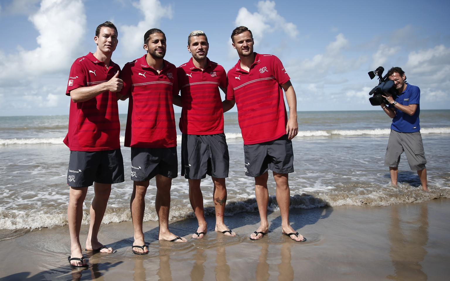 From left: Switzerland's Stephan Lichtsteiner, Ricardo Rodriguez, Valon Behrami and Haris Seferovic pose on the beach after a media conference of the Swiss national soccer team in Porto Seguro, Brazil, Tuesday, June 17, 2014. (KEYSTONE/Peter Klaunzer)