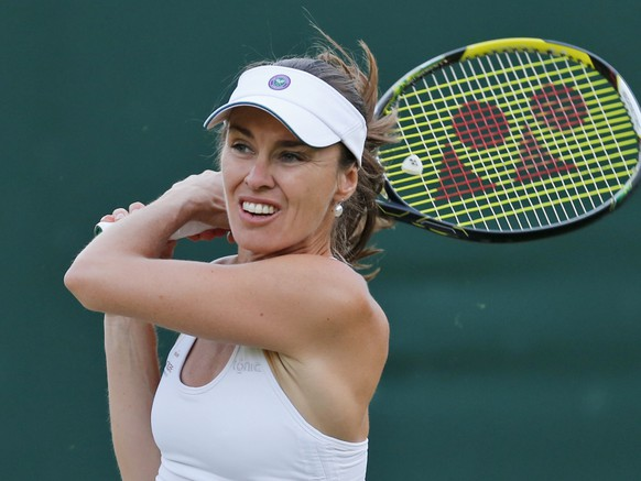 Martina Hingis of Switzerland, plays a return as she plays with partner Vera Zonareva of Russia against  Carla Black of Zimbabwe and Sania Mizra of India during their match at the All England Lawn Tennis Championships in Wimbledon, London, Wednesday, June 25, 2014. (AP Photo/Ben Curtis)
