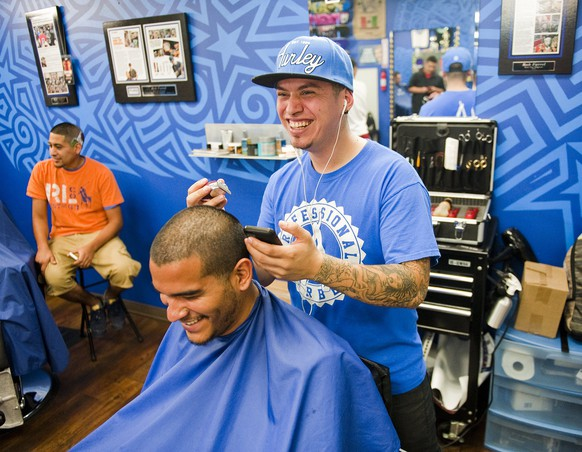 """Hair Artist and Master Barber Rob Ferrel (R), known as """"Rob the Original"""" cuts the likeness of Argentine soccer player Lionel Messi on the head of customer Vincent Hernandez, ahead of tomorrow's World Cup match between Argentina and Switzerland at his barbershop in San Antonio, Texas June 30, 2014.  REUTERS/Ashley Landis (UNITED STATES - Tags: SOCIETY SPORT SOCCER)"""