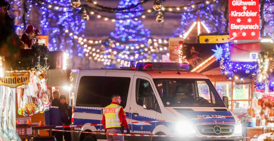 epa06362181 A police car and policemen stand behind barrier tape on an empty Christmas market after it was evacuated by police, in Potsdam, Germany, 01 December 2017. Police said they had found an explosive device at Potsdam Christmas market, a city near Berlin, and defused it.  EPA/FELIPE TRUEBA