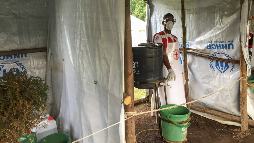 This photo taken Monday, June 10, 2019 and released by the International Rescue Committee (IRC), shows an Ebola screening checkpoint where people crossing from Congo go through foot and hand washing with a chlorine solution and have their temperature taken, at the Bunagana border crossing with Congo, in western Uganda. Uganda's health ministry said late Tuesday, June 11, 2019 that a child in Uganda has tested positive for Ebola in the first cross-border case of the deadly virus since an outbreak started in neighboring Congo last year. (Ben Wise/International Rescue Committee via AP)