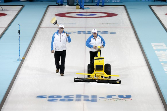 Hans Wuthrich, right, and Eric Montford, left, prepares the ice sheet between curling matches at the 2014 Winter Olympics, Sunday, Feb. 16, 2014, in Sochi, Russia. (AP Photo/Robert F. Bukaty)