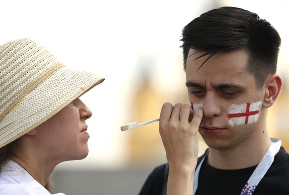 A soccer fan's face painted by a street artist in the colors of the England national flag outside the venue for the group G match between England and Panama at the 2018 soccer World Cup at the Nizhny Novgorod Stadium in Nizhny Novgorod, Russia, Sunday, June 24, 2018. (AP Photo/Darko Bandic)