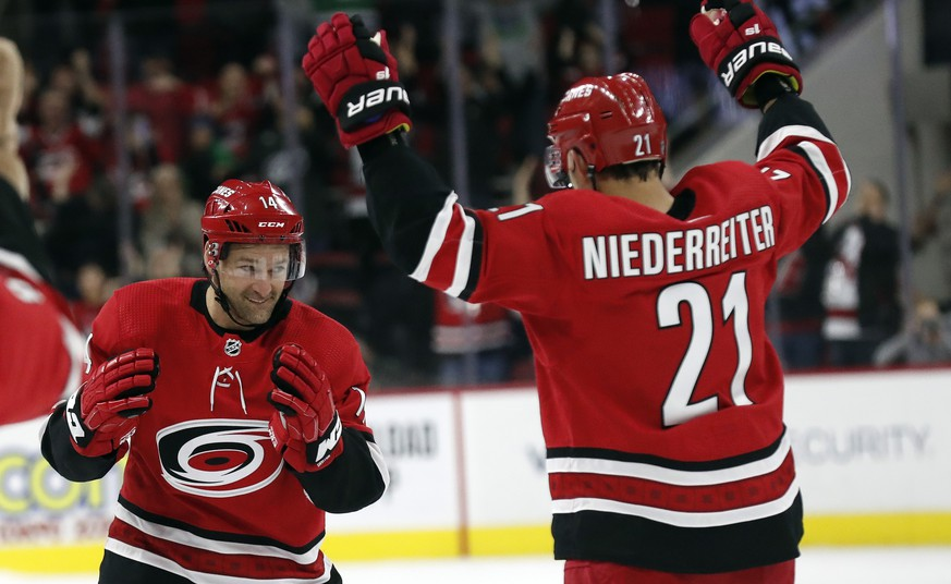 Carolina Hurricanes right wings Justin Williams, left, and Nino Niederreiter (21), of Switzerland, celebrate Williams' winning goal in a shootout against the Vancouver Canucks during an NHL hockey game in Raleigh, N.C., Sunday, Feb. 2, 2020. (AP Photo/Gerry Broome)
