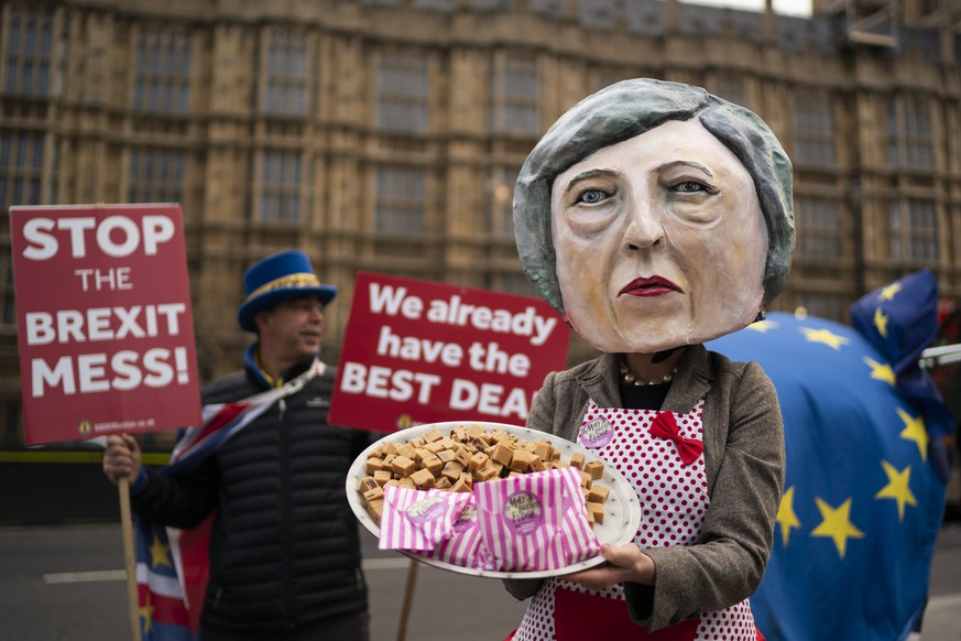 epa07221280 Anti-Brexit campaigner dressed as British Prime Minister Theresa May holding a plate of fudge poses for photographers outside Houses of Parliament in Central London, Britain, 10 December 2018. Prime Minister May faces a vote in the House of Commons tomorrow on her draft agreement with the European Union which is due to take the United Kingdom out of the European Union in March 2019.  EPA/WILL OLIVER