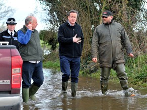 Prime Minister David Cameron, center, visits Goodings Farm in Fordgate, southwest England, with Bridgwater and West Somerset MP Ian Liddell-Grainger, left, and and farmer Tony Davy, right, Friday, Feb. 7, 2014. Flood-hit villagers have lambasted Britain's Environment Agency chairman Chris Smith where thousands of acres have been underwater for more than a month. Bouts of rain, high tides and strong winds have pounded Britain since December, and this week washed away a stretch of the main rail line linking London and the southwest. (AP Photo/Tim Ireland) POOL