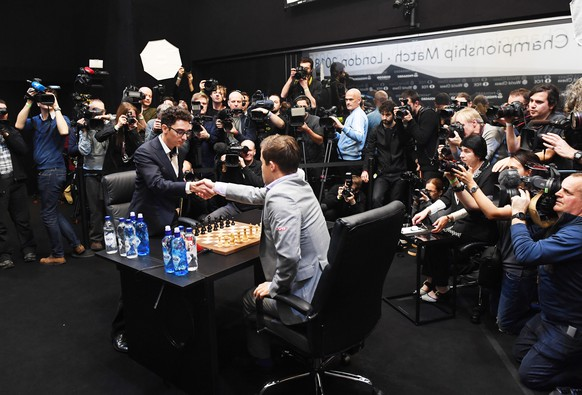 epa07195072 Norway's World Chess Champion Magnus Carlsen (C) plays against US challenger Fabiano Caruana (L) at the tie-break game during the World Chess Championship 2018 in London, Britain, 28 November 2018.  EPA/FACUNDO ARRIZABALAGA
