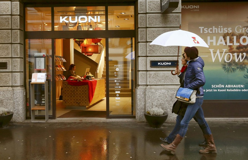 People walk past a travel bureau of Swiss travel group Kuoni Switzerland in Zurich January 14, 2015. Kuoni shares jumped 7 percent after saying it would exit from tour operating activities as it focuses on its core business as a service provider to global travel industry. REUTERS/Arnd Wiegmann (SWITZERLAND)