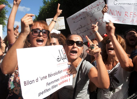 FILE - In this Oct.2, 2012 file photo, hundreds of Tunisian women protest  in support of a woman who says she was raped by police and is facing accusations of violating modesty laws in Tunis. A new poll of 50,000 people across 34 African countries finds attitudes toward women's equality are dimmest in the predominantly Muslim north. The poll by Afrobarometer, conducted between 2011 and 2013, found women in general are at a disadvantage compared to men, but support for women's equality is growing more widespread  Poster in foreground reads: 'Result of a revolution : stolen, women : raped, girls.