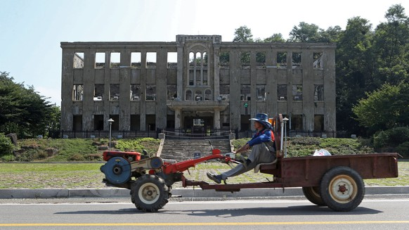 epa06182455 A farmer drives a tractor past the former Cheorwon office of the Workers' Party of Korea, the ruling party of North Korea, in the border town of Cheorwon, South Korea, 04 September 2017. North Korea on 03 September announced it has conducted to its sixth nuclear test by detonating a hydrogen bomb that can installed in an intercontinental ballistic missile (ICBM).  EPA/YONHAP SOUTH KOREA OUT